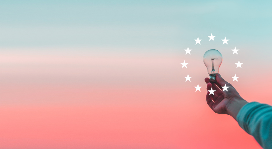 A person holds a light bulb surrounded by the 12 stars of the European Union flag.